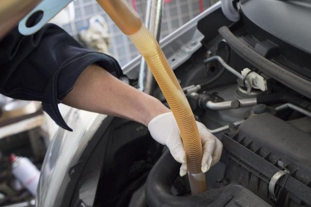 車のエンジンオイルを注ぐ作業